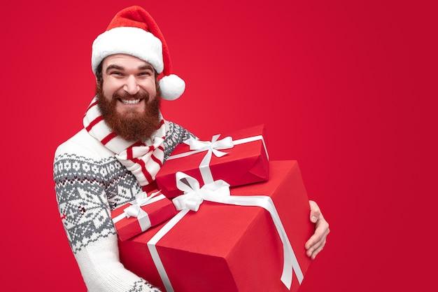 Uomo con la barba che indossa il cappello della santa e che tiene grande mucchio di regali avvolti