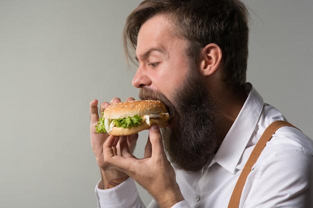 Uomo con la barba in camicia bianca e bretelle che mangia cibo spazzatura da un fast food hamburger o cheeseburger su sfondo grigio