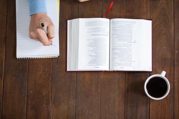 Uomo con una bibbia che scrive sul blocco note