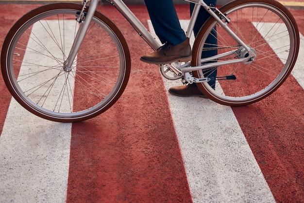 Uomo con la bicicletta che attraversa la strada in città