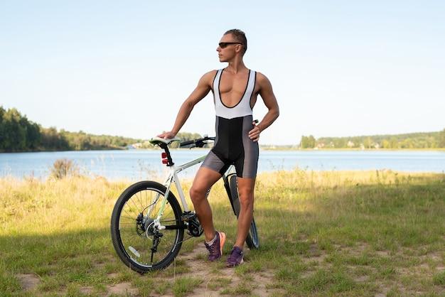 Un uomo con una bicicletta nella natura, in un campo. per qualsiasi scopo.