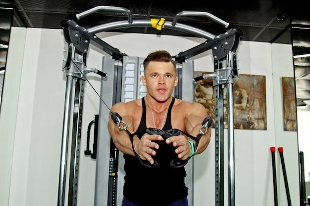 Un uomo con grandi muscoli è impegnato nel sollevamento pesi in palestra. un atleta esausto si dedica allo sport su simulatori di pesi massimi. esercizi sportivi.