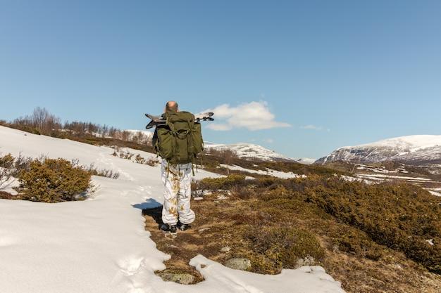 Uomo con grandi ciaspole nel suo zaino, visto da dietro, camminando verso le montagne dovre in norvegia