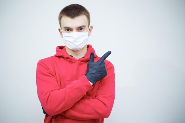 Uomo con guanti neri e maschera di medicina che mostra in una direzione. immagine per il lavoro di copia spazio. uomo che si protegge dal virus pandemico mondiale.