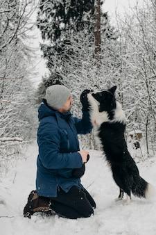 Uomo con un cane border collie bianco e nero nella neve