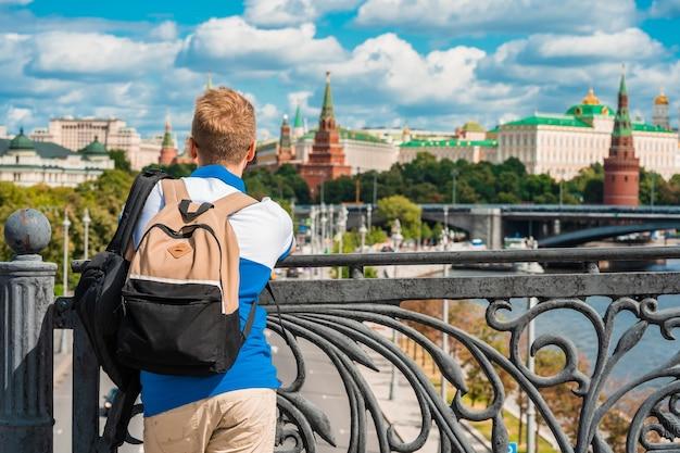 Un uomo dai capelli biondi si trova su un ponte che domina il cremlino e il fiume a mosca