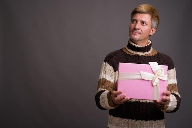 Uomo con capelli biondi che indossa maglione a collo alto isolato contro il muro grigio