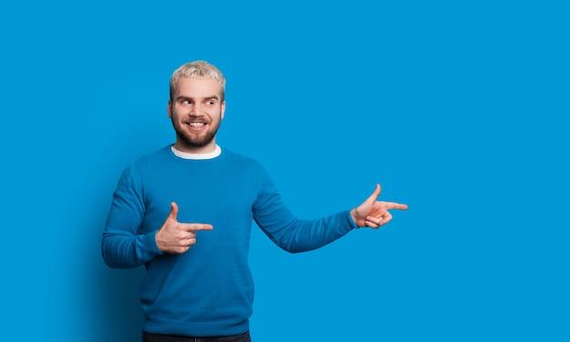 L'uomo con i capelli biondi punta a destra