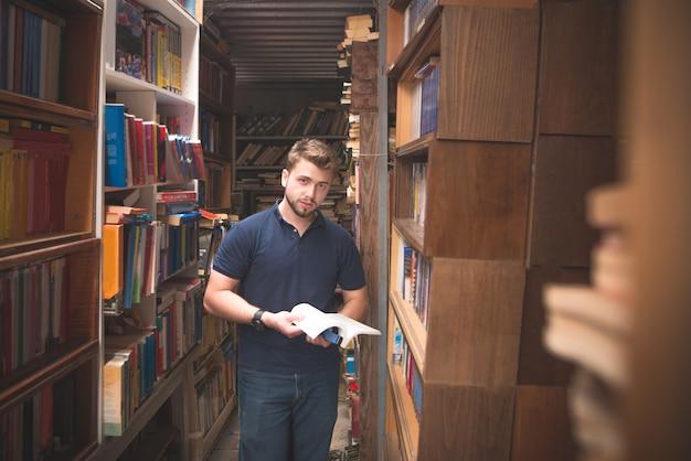 L'uomo con un libro tra le mani si trova in una biblioteca pubblica