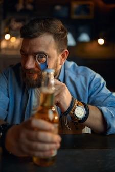 Uomo con bottiglia di birra seduto al bancone del bar