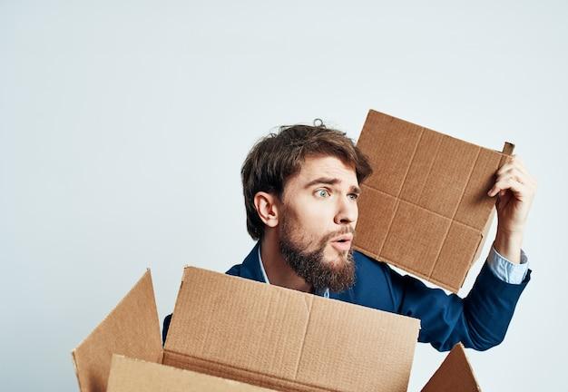 Uomo con scatole in gruppi che si spostano in un nuovo luogo di lavoro ufficiale di stile di vita
