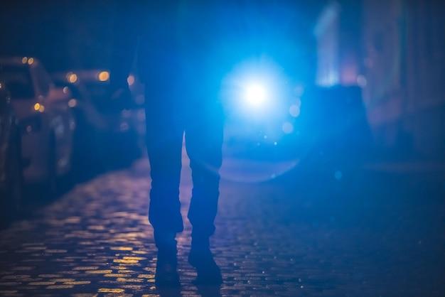L'uomo con una torcia luminosa sta sulla strada. serata notturna