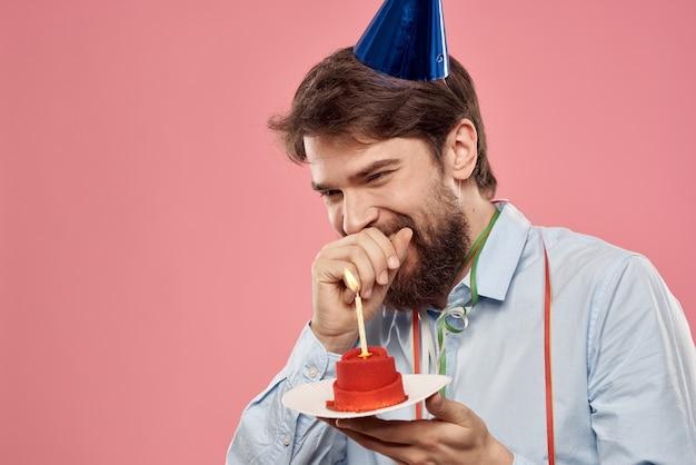Uomo con una torta con una candela e un berretto di compleanno su una rosa