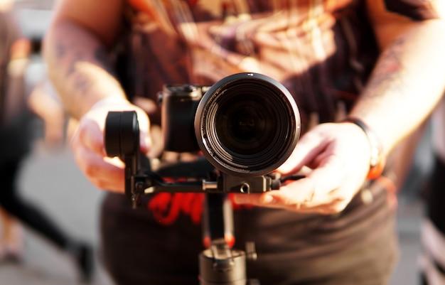 Un uomo con una macchina fotografica e una fotocamera con obiettivo per le riprese video