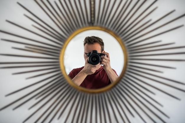 Uomo con la macchina fotografica che prende immagine della riflessione