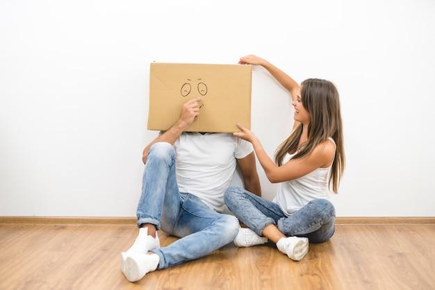 L'uomo con una scatola di cartone sulla testa si siede vicino alla donna