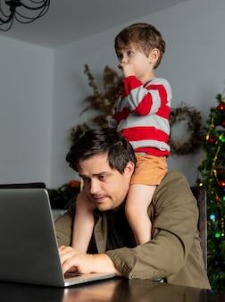L'uomo con un bambino sta lavorando sodo con il laptop in ufficio a casa durante la pandemia