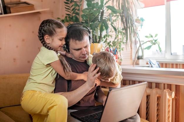 Uomo con bambini che utilizzano laptop e auricolari durante il lavoro a casa, la vita in quarantena