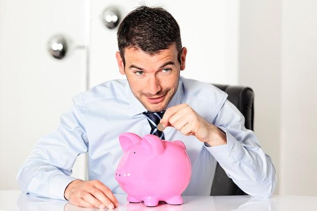 Uomo con moneta e salvadanaio rosa