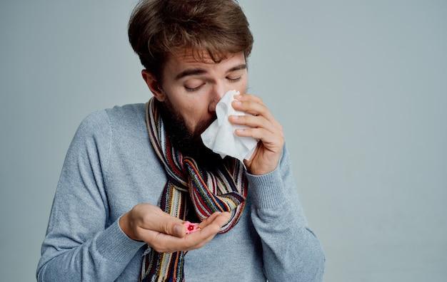 Un uomo con un raffreddore che tiene una pillola influenza problema di salute
