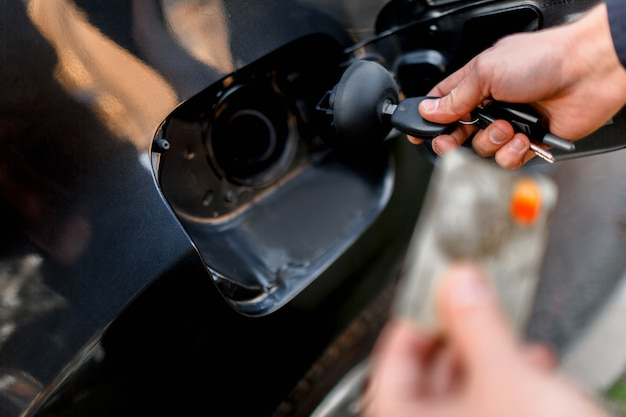 Uomo con la carta di credito aprendo il serbatoio della sua nuova auto. calcolo del denaro senza contanti. carburante, benzina olio, diesel, concetto di gas