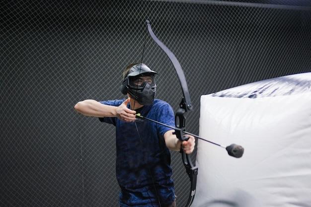 Uomo con arco di frecce di balestra. l'arciere prende la mira, tiratore scelto. club di balestra.