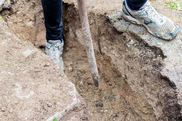 L'uomo con un piede di porco schiaccia il terreno duro mentre scava un fossato in un cantiere edile