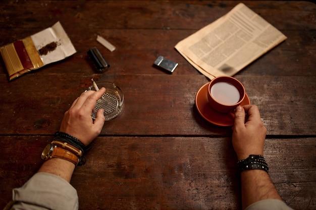 L'uomo con la tazza di caffè fuma una sigaretta al tavolo di legno, vista dall'alto. cultura del fumo di tabacco, sapore specifico. svaghi fumatori maschi