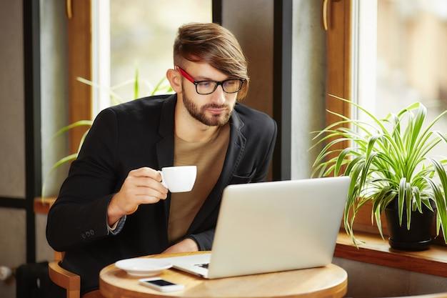 Uomo con la tazza al computer portatile