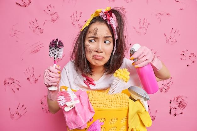 L'uomo con i capelli scuri pettinati tiene la spazzola sporca dopo aver pulito la toilette detergente chimico fa un sorrisetto il viso si trova vicino al cesto pieno di biancheria isolato sul rosa