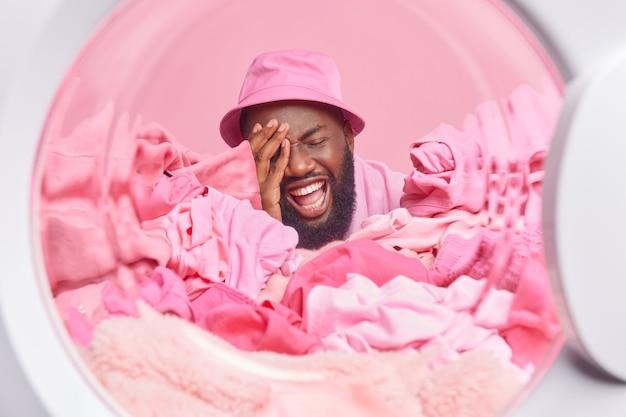 L'uomo con la pelle scura ride positivamente posa intorno a un assortimento di biancheria rosa carica la lavatrice prima del lavaggio indossa panama sulla testa fa le faccende quotidiane a casa