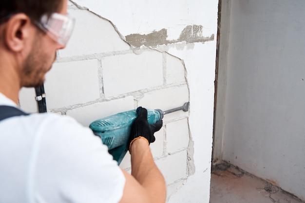 Uomo con martello demolitore rimuovendo stucco dalla parete