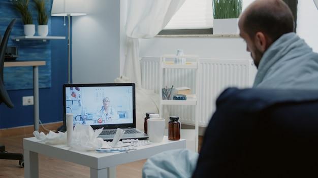 Uomo con malattia che utilizza la videochiamata per la telemedicina