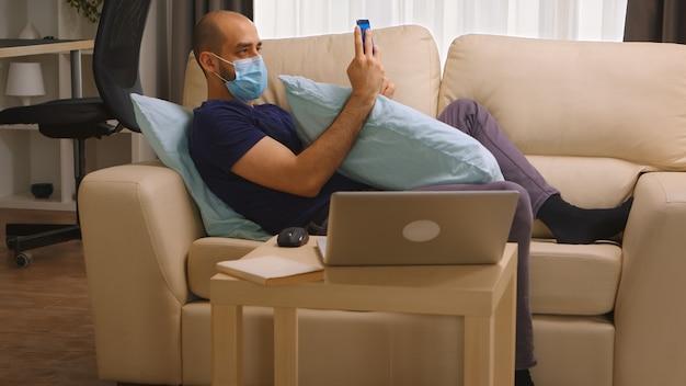 Uomo con maschera usa e getta sul divano che cerca informazioni sul suo smartphone sull'epidemia di coronavirus in tutto il mondo.