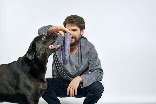 Uomo con anello grigio di addestramento del cane che fa luce degli animali domestici di esercizi