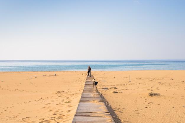 Uomo con cane che cammina sulla spiaggia tropicale.