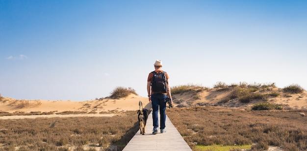 Uomo con cane che cammina sul sentiero di legno sulla spiaggia e guarda in lontananza l'oceano.