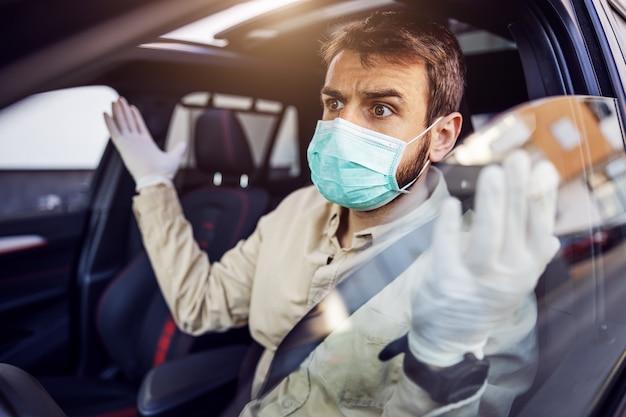 Uomo con maschera e guanti alla guida di un'auto. prevenzione delle infezioni e controllo dell'epidemia. pandemia mondiale. rimanga sicuro.