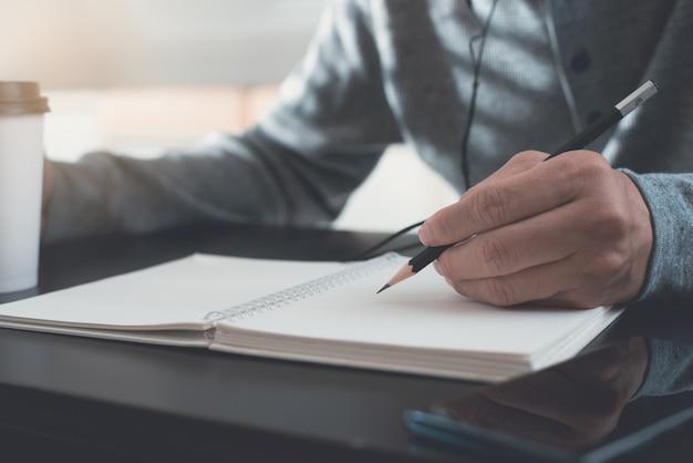 Uomo con auricolare apprendimento online e scrittura su notebook