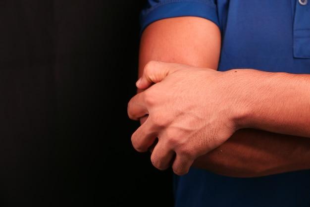 Uomo con dolore al gomito isolato in nero. concetto di sollievo dal dolore.