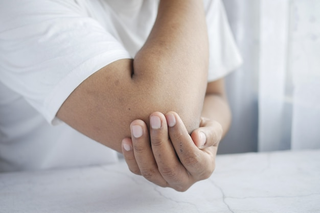 Uomo con il concetto di sollievo dal dolore al gomito