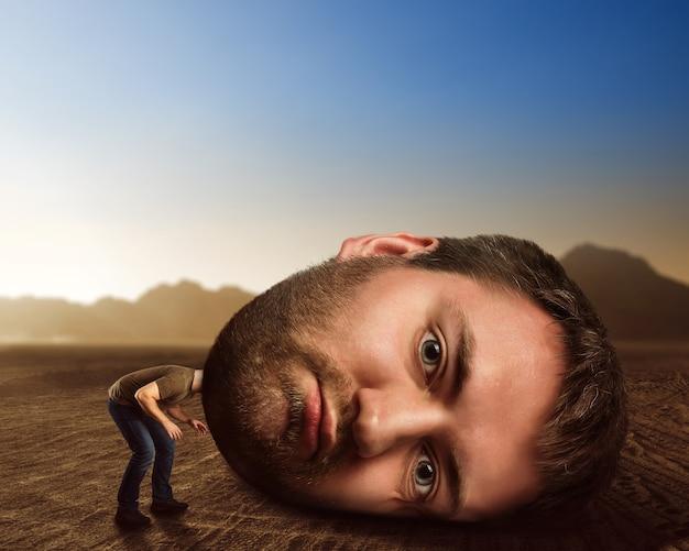 Uomo con una testa enorme nel deserto