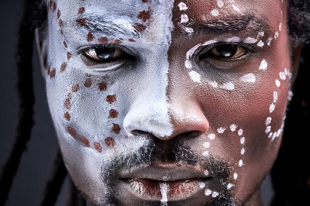 Uomo con dipinti etnici sul viso