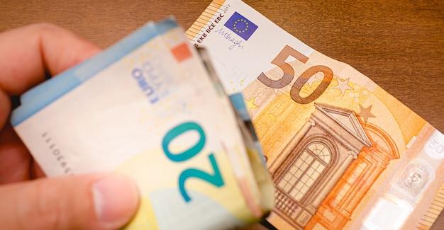 Un uomo con banconote in euro in primo piano con cinquanta banconote in euro su una scrivania in legno