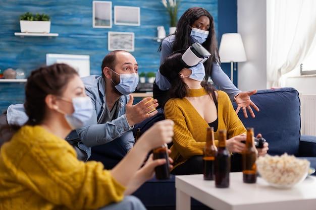 Uomo con maschera facciale che si rallegra per gli amici che giocano ai videogiochi con auricolare vr nel soggiorno di casa mantenendo le distanze sociali in tempo di pandemia globale con covid. persone multietniche che si divertono.