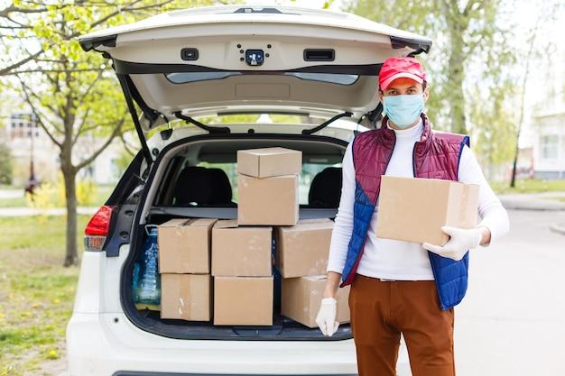 L'uomo con la maschera facciale sta consegnando cibo e generi alimentari durante l'epidemia di virus.