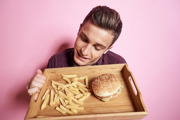 Uomo con fast food mangiare hamburger patatine fritte su uno sfondo rosa.