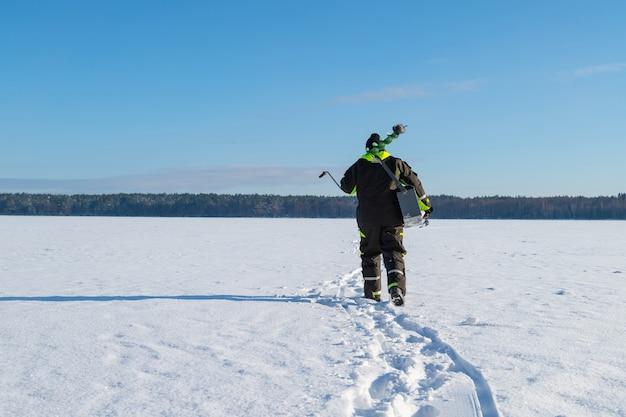 Uomo con attrezzatura da pesca che cammina su un lago ghiacciato in lontananza in una soleggiata giornata invernale.