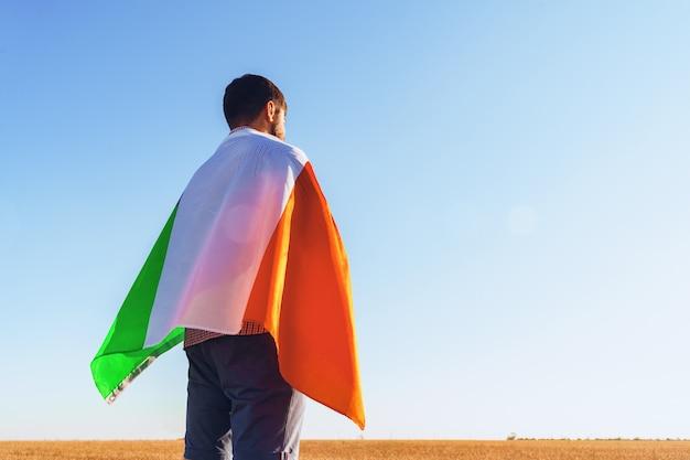 Uomo con una bandiera dell'italia in piedi in campo