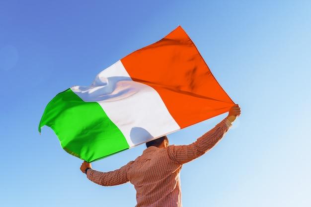 Uomo con una bandiera dell'italia in piedi nel campo mattina
